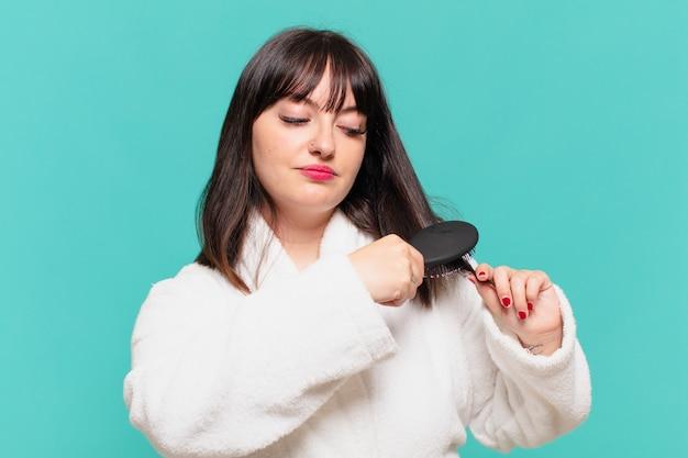 Giovane bella donna che indossa un'espressione arrabbiata in accappatoio e tiene in mano una spazzola per capelli