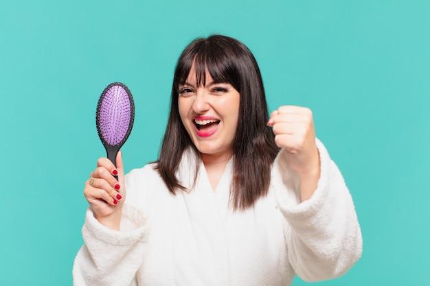 Giovane bella donna che indossa un accappatoio che celebra con successo una vittoria e tiene in mano una spazzola per capelli