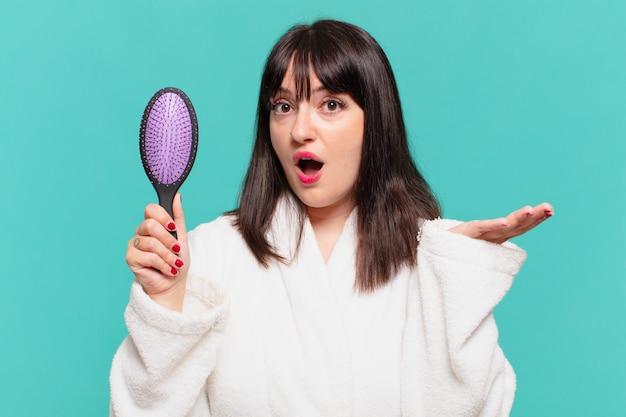 Giovane bella donna che indossa un accappatoio dubbioso o espressione incerta e tiene in mano una spazzola per capelli