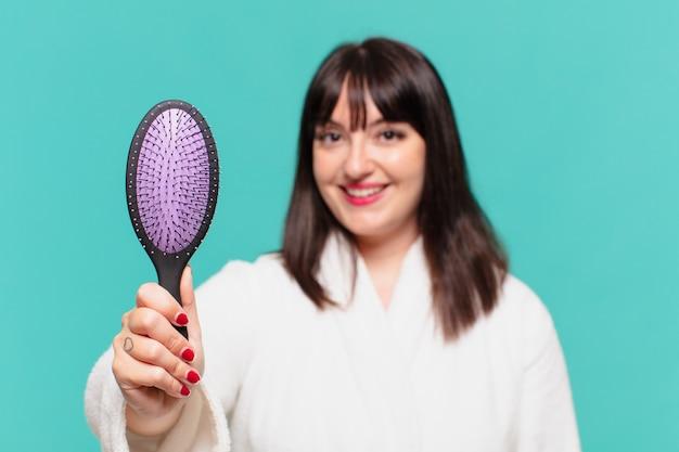 Giovane bella donna che indossa un accappatoio felice espressione e tiene in mano una spazzola per capelli