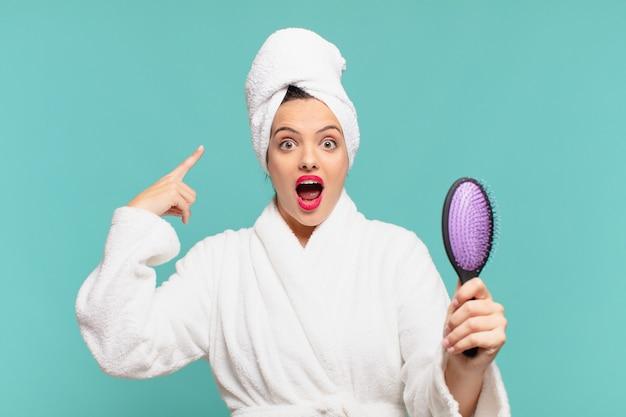 Giovane bella donna che indossa un'espressione spaventata in accappatoio e tiene in mano una spazzola per capelli