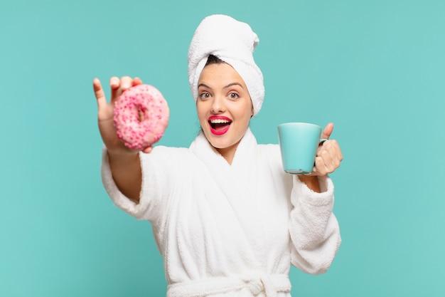 Giovane bella donna che indossa un'espressione sorpresa in accappatoio e fa colazione