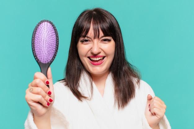 Giovane bella donna che indossa accappatoio con espressione felice e tiene in mano una spazzola per capelli