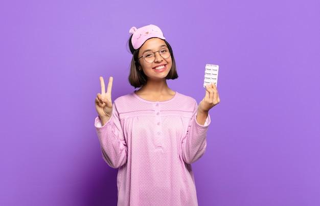 Giovane donna graziosa che indossa pigiami e azienda pillole