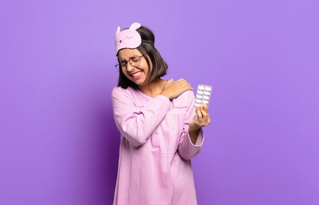 Giovane bella donna che indossa un pigiama e tiene in mano pillole