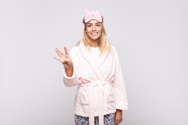 Giovane donna graziosa che indossa il pigiama, sorridente e dall'aspetto amichevole, mostrando il numero quattro o quarto con la mano in avanti, contando alla rovescia