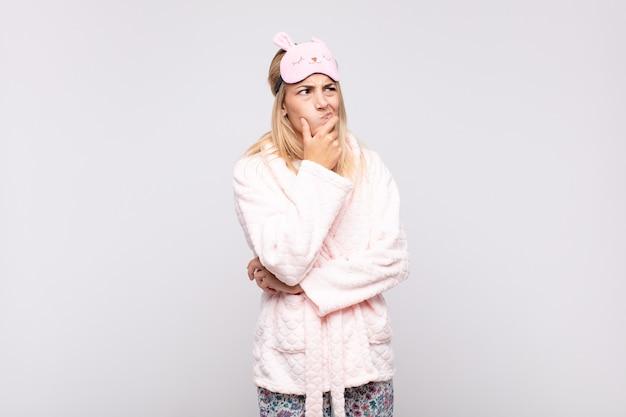 Giovane bella donna che indossa il pigiama, pensa, si sente dubbiosa e confusa, con diverse opzioni, chiedendosi quale decisione prendere