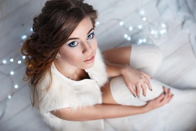 Giovane donna graziosa in calzini lavorati a maglia bianchi che si siedono sul pavimento su una delle luci