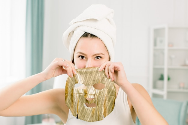 Giovane donna graziosa in asciugamano bianco dopo il bagno che tiene la maschera facciale dell'oro di carta. donna che ottiene la maschera facciale d'oro.