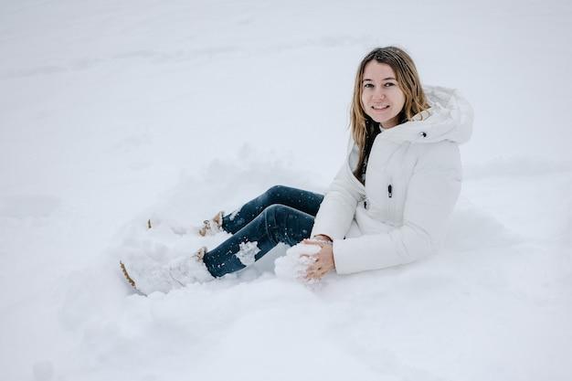 Giovane donna graziosa in abiti invernali si siede su un cumulo di neve e sorride