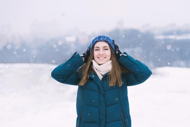Giovane donna graziosa in abiti invernali sorridendo.