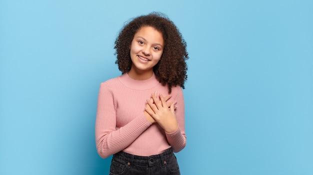 Giovane donna graziosa con capelli afro e maglione rosa in posa sulla parete blu