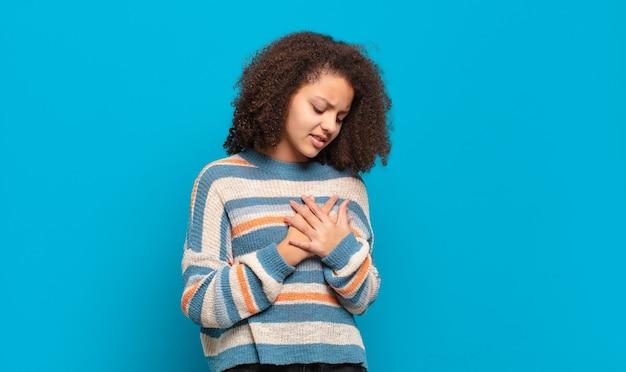 Giovane donna graziosa con capelli afro e maglione a righe in posa sulla parete blu