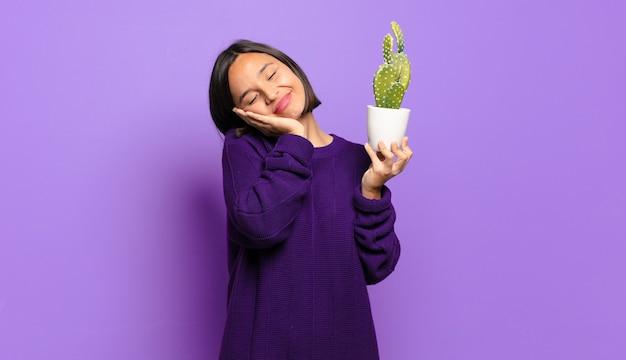 Giovane donna graziosa con un cactus