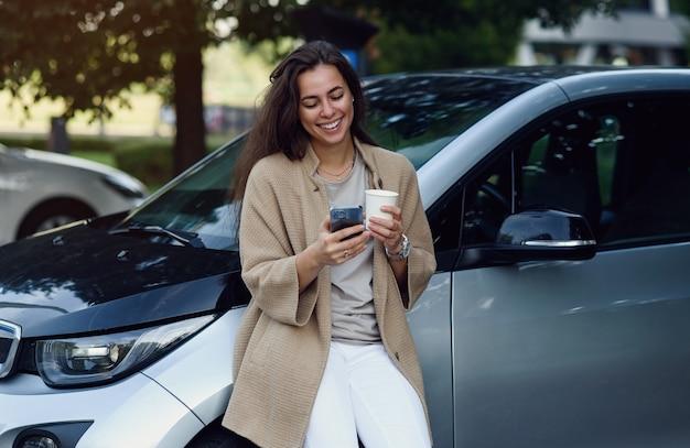 Giovane bella donna con una tazza di caffè e un blog di messaggistica su tablet nel parco autunnale vicino al veicolo