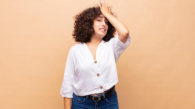 Giovane bella donna con i capelli ricci e una camicia bianca