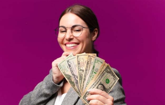Giovane donna graziosa con banconote in dollari