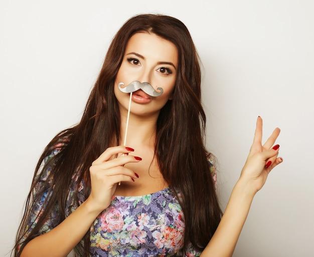 Giovane bella donna con baffi finti.