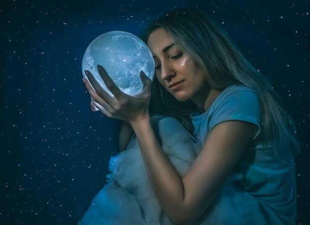 Giovane donna graziosa con la luna piena e le nuvole sul primo piano blu stellato del fondo