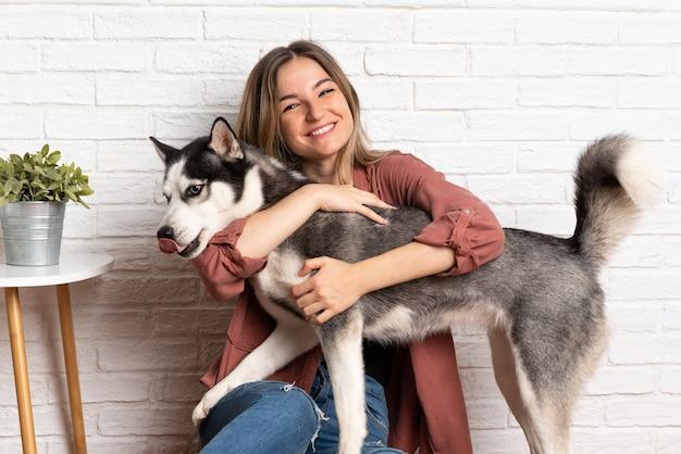 Giovane donna graziosa con il suo cane husky seduto sul pavimento al chiuso