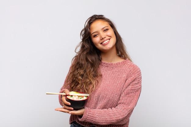 Giovane donna graziosa con le tagliatelle che sorride allegramente, sentendosi felice e mostrando un concetto nello spazio della copia con il palmo della mano