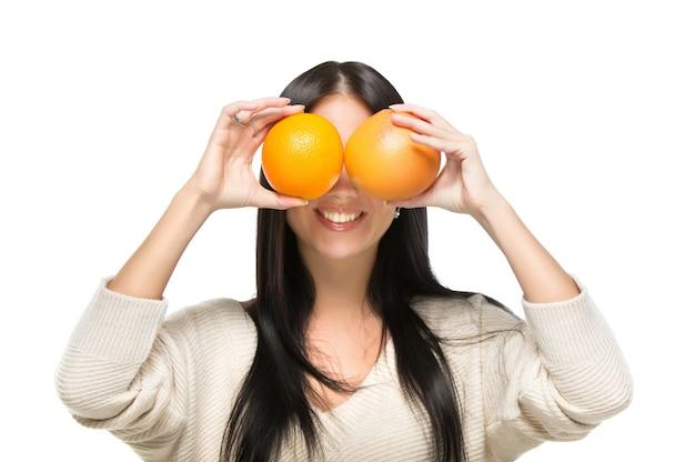 Giovane donna graziosa con l'arancio