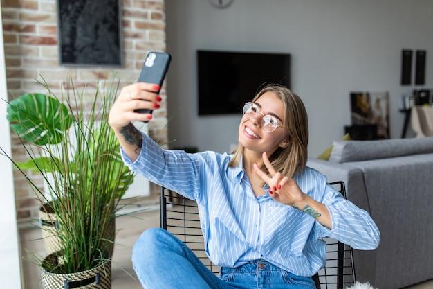 Giovane donna graziosa con il gesto di pace che si siede nella sedia che prende selfie vicino alla finestra a casa.