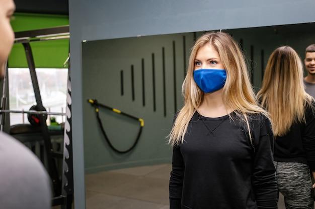 Giovane donna graziosa con maschera protettiva che lavora con personal trainer in palestra durante la pandemia covid-19. persona sportiva in maschera protettiva.