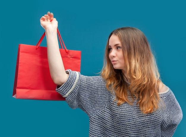 Giovane donna graziosa con i sacchetti della spesa.