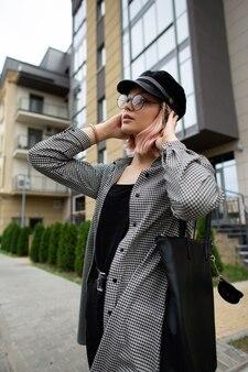 Giovane bella donna con occhiali vintage e un cappello in una camicia a quadri alla moda con una borsa in pelle nera cammina per strada vicino all'edificio