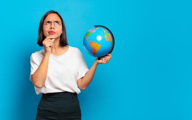 Giovane donna graziosa con una mappa del globo del mondo
