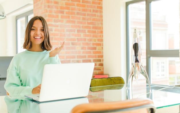 Giovane bella donna che lavora, si sente felice, sorpresa e allegra, sorridente con atteggiamento positivo, realizzando una soluzione o un'idea