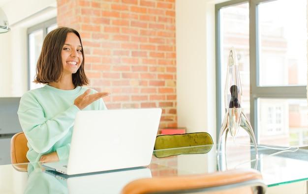 Giovane donna graziosa che lavora, sorride allegramente, si sente felice e mostra un concetto nello spazio della copia con il palmo della mano