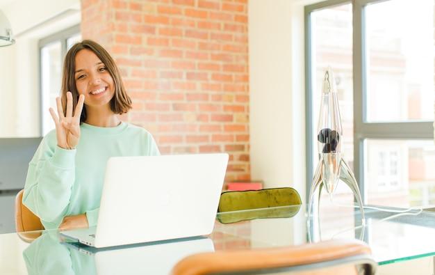 Giovane donna graziosa che lavora, sorride e sembra amichevole, mostrando il numero quattro o quarto con la mano in avanti, contando alla rovescia