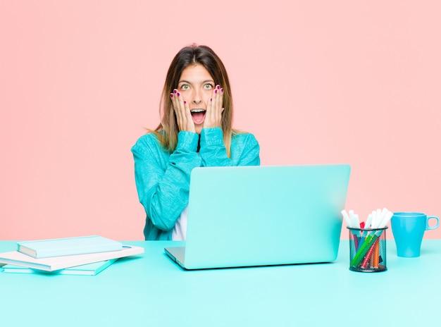 Giovane donna graziosa che lavora con un computer portatile sentirsi scioccato e spaventato, guardando terrorizzato con la bocca aperta e le mani sulle guance