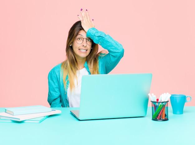 Giovane bella donna che lavora con un computer portatile alzando il palmo alla fronte pensando oops, dopo aver fatto uno stupido errore o aver ricordato, sentendosi stupido