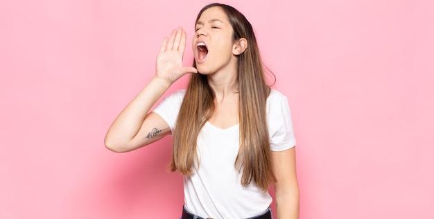 Giovane donna graziosa che urla ad alta voce e con rabbia per copiare lo spazio sul lato, con la mano vicino alla bocca