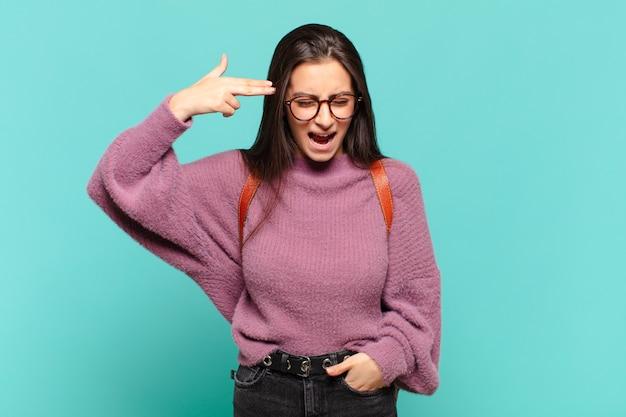 Giovane predonna che sembra infelice e stressata, gesto suicida che fa il segno della pistola con la mano, indicando la testa. concetto di studente