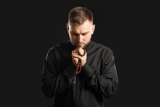 Giovane sacerdote che prega dio sul muro scuro