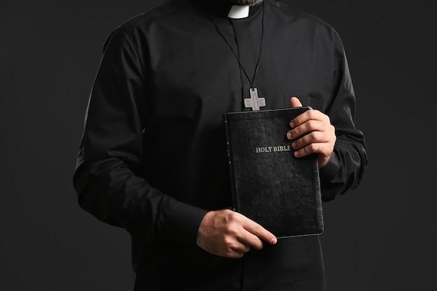 Giovane sacerdote con la bibbia su sfondo scuro