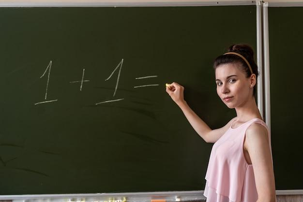 Giovane insegnante femminile primaria scritta sulla lavagna uno più uno, concetto di istruzione