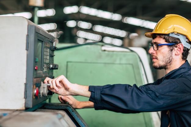 Il giovane ingegnere tecnico di professione fa funzionare la macchina pesante al cnc automatizzato in fabbrica, mano del lavoratore del primo piano.