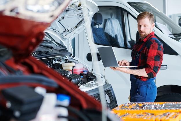 Giovane riparatore professionista del servizio auto con laptop che naviga in rete o prende ordini online in officina o hangar