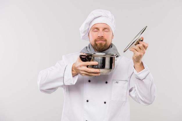 Giovane chef professionista che gode del buon odore di zuppa o altro pasto cucinato in padella mentre si trova in isolamento