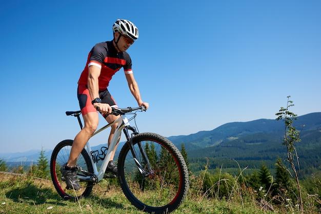 Giovane ciclista professionista che guida la bici sulla collina erbosa. montagne e cielo estivo blu. stile di vita attivo e concetto di sport estremo