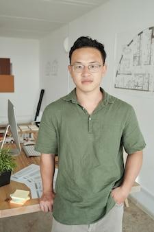 Giovane designer professionista in piedi contro il suo posto di lavoro