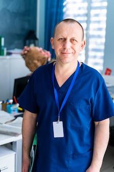Giovane medico o chirurgo professionista in uniforme in piedi davanti alla telecamera sullo sfondo dei suoi colleghi che lavorano