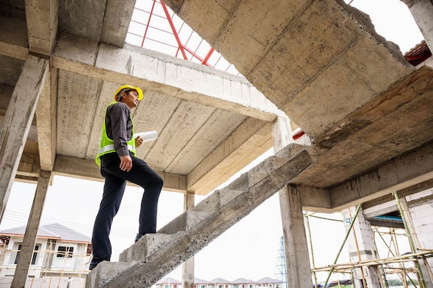 Giovane operaio ingegnere professionista in casco protettivo e cianografie carta a disposizione presso il cantiere edile
