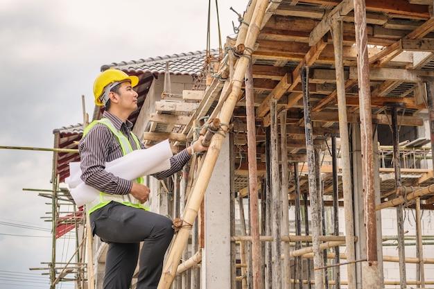 Operaio giovane ingegnere professionista in casco protettivo e cianografie carta a portata di mano lavorando su scala presso il cantiere edile