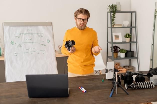 Giovane fotografo professionista in abbigliamento casual guardando la fotocamera dello smartphone e il display del laptop mentre parla al pubblico online